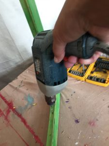 A picture of of a Black and Decker power drill drilling holes into a green frame
