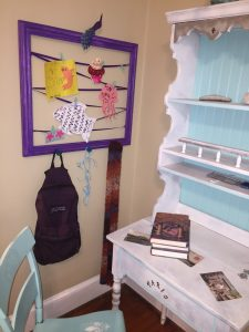 A picture of a purple frame with a zig zag purple ribbon attached to it that holds different cards and children's projects and it has a backpack hanging from the bottom. Next to it is a white desk and a blue chair