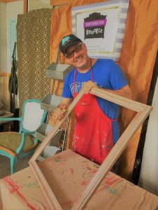 Tim Kime (a man with glasses in a red smock, blue shirt, and black cap) sanding a large picture frame