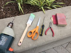 Different tools needed for the DIY frames project. These include a power drill, paint brush, scissors, a screw driver, and pliers