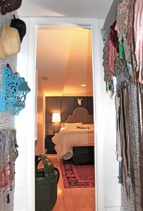 A picture from the inside of the closet out into the bedroom. In the bedroom there is a bed with a white comforter, a large headboard, a red carpet, a cow skill above the bed, wooden floors, and a side table with a lamp