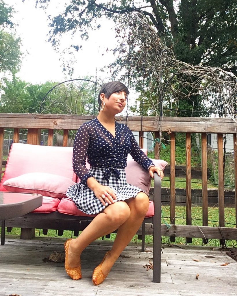 A picture of a woman with short dark hair sitting outside on a patio on a seat with pink coushions. She is wearing a sheer long-sleeved top, colored with navy blue and taupe polka dots, by Italian high-end designer, Fuzzi and a vintage houndstooth black and white skirt,