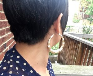 A picture of a woman with short dark hair. It is the back of her head. She is wearing a pair of gold, bone, door knocker, hoop earrings