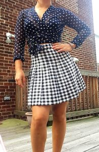 A picture of a woman from the neck down. She is wearing a sheer long-sleeved top, colored with navy blue and taupe polka dots, by Italian high-end designer, Fuzzi and a vintage houndstooth black and white skirt,