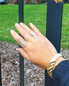 A picture of the back of the DC Goodwill Fashionista's hand. She is wearing a copper ring that covers most of her pointer finger that has designs cut into it. She is also wearing a ring on her ring finger that has an oval shape and has a slit cut into it. She is wearing a gold twist bracelet on her wrist. In the background is a black fence and the ground has mulch on it an there is green grass.