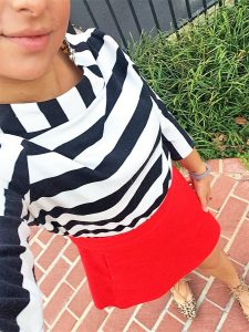 A picture of the DC Goodwill Fashionista. She is taking a top down selfie and you can see her mouth and chin and the whole front of her body. She is wearing a black and white striped boatneck shirt, a red skirt, and a pair of leopard print shoes. She is standing on a brick sidewalk with some grass and a fence in the background
