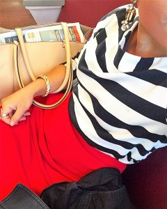 A picture of the DC Goodwill Fashionista. She is taking a top down selfie and you can see her mouth and chin and the whole front of her body. She is wearing a black and white striped boatneck shirt, a red skirt, a gold twisted bracelet, and has a tan purse and dark coat next to her. She is sitting on the Metro train