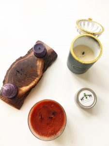 """A top down view of five candles. One with Two small purple tea candles on either end of a larger wooden natural looking candle holder. Another of a ceramic cylinder containing a candle. The ceramic is white and has a blue, gold, and black chevron pattern on it. In the center there is a black label with the words """"Maison"""" in gold and """"Sandalwood"""" in blue. Another of an orange candle in a glass, cylinder container. On the front there is a label saying Yankee Candle with a picture of pumpkins and the words """"Spiced Pumpkin"""" on it. And the last and smallest one is of a small cylinder shaped tin (shown from the top down). On the top it has a white label with two black elephants with a green tree in between them. The words """"One Kings Lane"""" is written in all capital letters and the website www.allkingslane,com is under the capitalized words"""