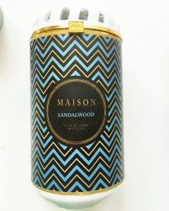 """A picture of a ceramic cylinder containing a candle. The ceramic is white and has a blue, gold, and black chevron pattern on it. In the center there is a black label with the words """"Maison"""" in gold and """"Sandalwood"""" in blue"""