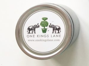 """A picture of a small cylinder shaped tin (shown from the top down). On the top it has a white label with two black elephants with a green tree in between them. The words """"One Kings Lane"""" is written in all capital letters and the website www.allkingslane,com is under the capitalized words"""
