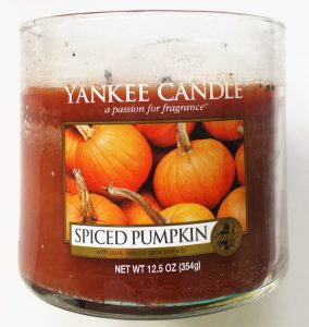 """A picture of an orange candle in a glass, cylinder container. On the front there is a label saying Yankee Candle with a picture of pumpkins and the words """"Spiced Pumpkin"""" on it."""