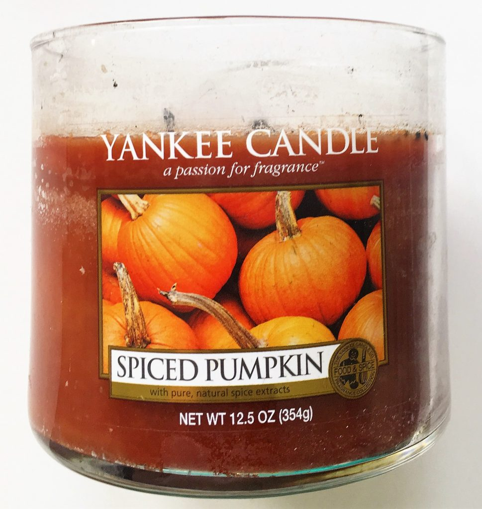 "A picture of an orange candle in a glass, cylinder container. On the front there is a label saying Yankee Candle with a picture of pumpkins and the words ""Spiced Pumpkin"" on it."