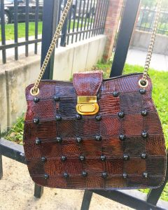 A picture of a brown purse with a gold chain hanging from a black metal fence. It is made out of brown, leather squares and has black studs and a gold clasp.