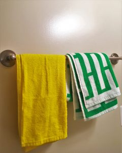 A picture of two shower towels. One is yellow and the other has a green and white pattern on it