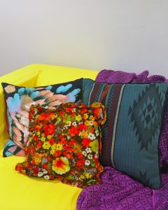 A picture of three pillows on a yellow couch with a purple blanket on it. In the center there is a brown pillow with a red and yellow floral pattern. On the right there is a pillow with a native american like pattern on it that is a dark shade of green with some brown, black, and red stripes. And on the left there is a pillow that is black but has blue and light brown paint stroke like patterns on it.