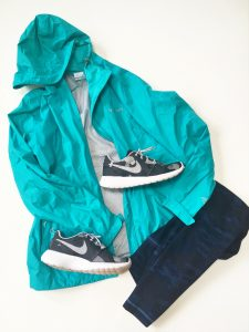 A picture of a blueish green, Arcadia-style, Columbia raincoat in a size small, a pair of gray and white Nike running shoes, and a pair of dark blue camo workout leggings