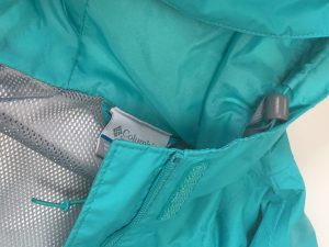 A picture of a blueish green, Arcadia-style, Columbia raincoat. It is a close up of the hood, tag, inner gray mesh, and the drawstring for the hood