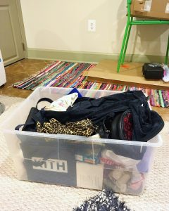 A large, plastic, storage bin that has a variety of items in it like clothing and bags. The bin looks like it has been used for moving. It is on top of a white carpet and there is a multicolor carpet in the background and a green chair.