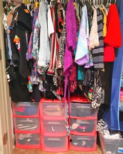 A picture of a closet. There is a large number of hanging clothes and below them are nine stackable plastic pink drawers. You can see inside the drawers and there are various clothing items in them.