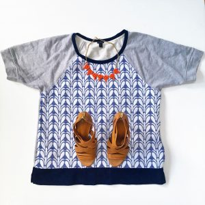 A picture of three items: a size large, quilted, blue and gray, patterned, baseball-style, short sleeved J Crew top, a pair of leather strap pump heels, and a salmon colored baulb necklace