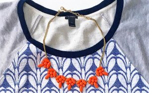 A close up of the salmon colored baulb necklace against the J Crew top