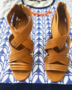 A picture of three items: a size large, quilted, blue and gray, patterned, baseball-style, short sleeved J Crew top, a pair of leather strap pump heels, and a salmon colored baulb necklace. A close up of the shoes