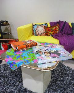 A side table in front of a yellow couch on top of a black, white, and gray shag carpet. It has various colorful books and a cloth on top as well as a pair of glasses. The table itself has a retro style to it and has a white bottom and brown top