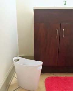 A small white trash can in a bathroom. You can see the brown sink cabinet and pink bath mat