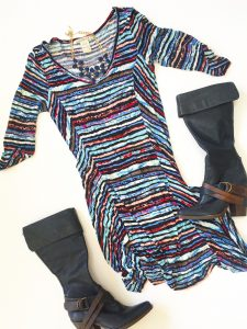 A picture of a high-low dress with watercolors like pink, blue, purple and black print in a size large. Also pictured are a pair of tall, black, leather boots