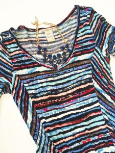 A picture of the top of a high-low dress with watercolors like pink, blue, purple and black print in a size large. Also pictured is a blue, bulb necklace