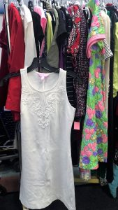 A picture of a rack of clothing in a Goodwill retail store. A white, sleeveless dress is not hanging with the rest of the clothes and is shown more prominent in the picture
