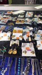 A picture of a jewelry case in a Goodwill retail store. There are various earrings shown within the case