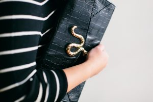A picture of a woman's arm holding a black, leather, faux alligator skin, clutch purse with a gold snake ornamenting it.