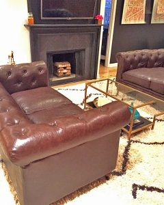 A picture of a living room with leather couches, a coffee table with a frame and glass top, a fireplace, and a white carpet