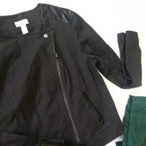 A close up of the black moto jacket. The zipper and button are clearer as well as the tag that says LOFT. The corner of the hunter green pants are also seen