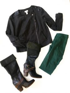 A picture of four items: a black moto jacket with leather patches in different places and a zipper, a pair of hunter green jeans, and a pair of black boots with brown leather straps and short heels