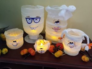 A picture of five glass containers wrapped to look like a mummy family as Halloween decorations. There is a father with blue glasses, a mother with a bow, a daughter with pig tails, a son with large front teeth, and a dog with floppy ears. They have been made wrapped with gauze