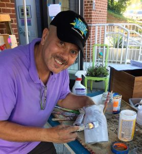 A picture of Tim Kime (a man wearing a black baseball cap and a purple shirt with a goatee working on one of the DIY mummies. He is smiling at the camera