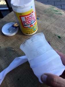 A picture of a vase being wrapped in gauze using mod podge. You can see the mod podge in the background