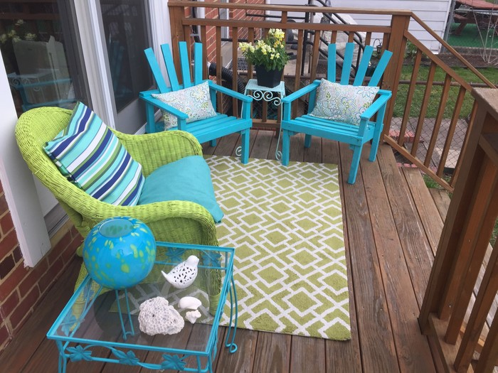 Tim stages upcycled chairs, plant stand, coffee table, and decorative items on patio