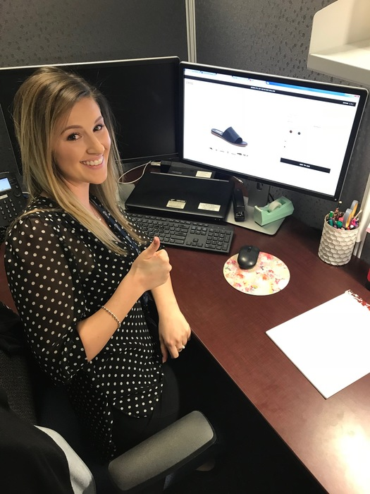 Karen's co-worker, Megan, smiles while shopping online for open-toed mules