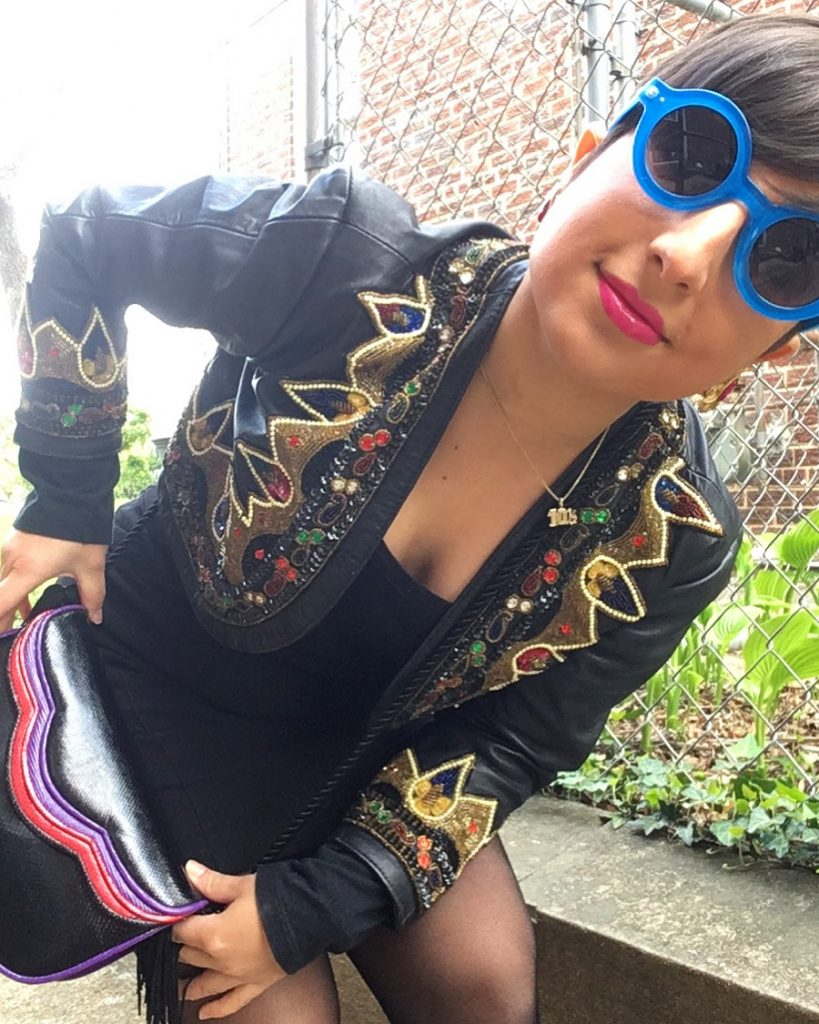 Carolyn models a vintage leather cross body bag, embellished faux leather jacket, and blue Lennon-style shades