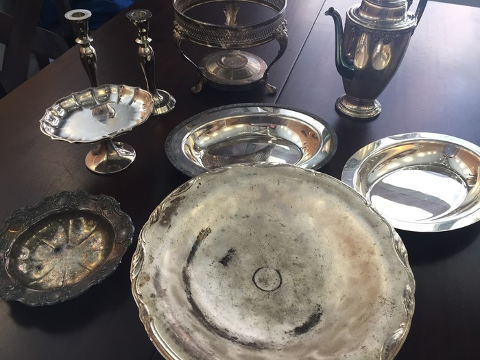 Tim's collection of antique serving trays, platters, and candlestick holders found at a local Goodwill