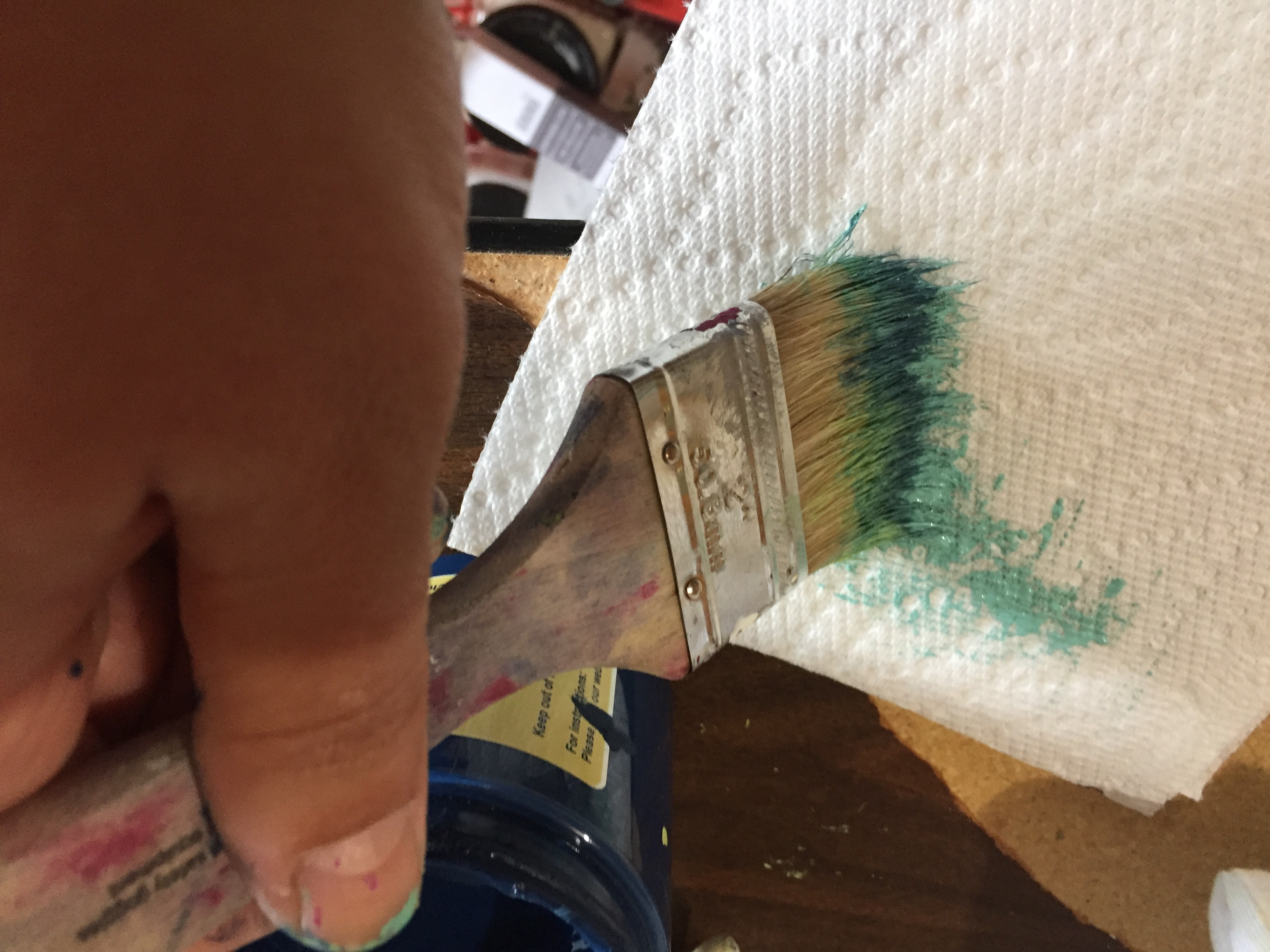 Courtney dabs the paint brush on a paper towel