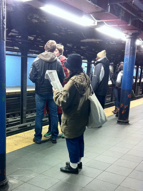 Woman dressed in winter gear including cropped pants waiting for the NY subway
