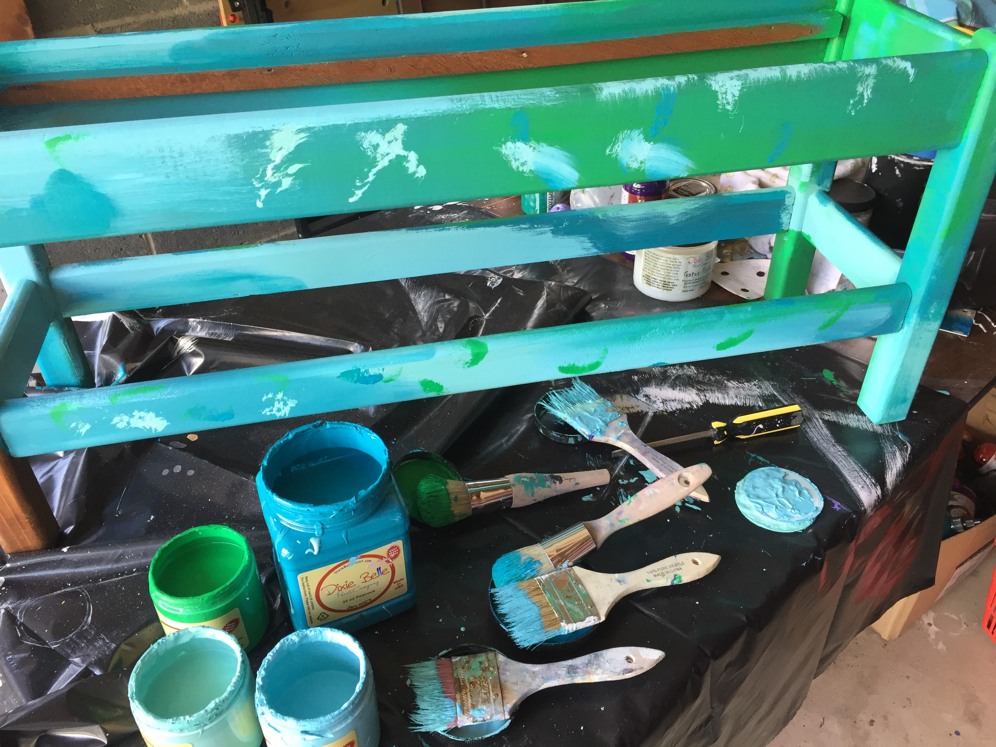 Courtney paints the bench several shades of blue as well as green