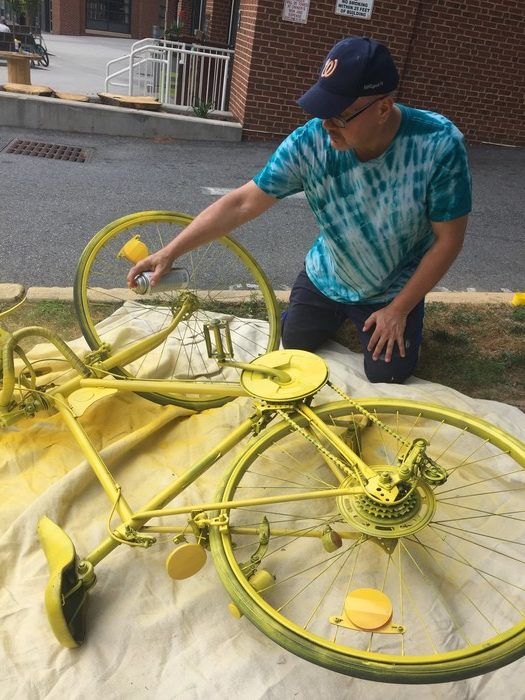 Tim spray paints the bicycle yellow.