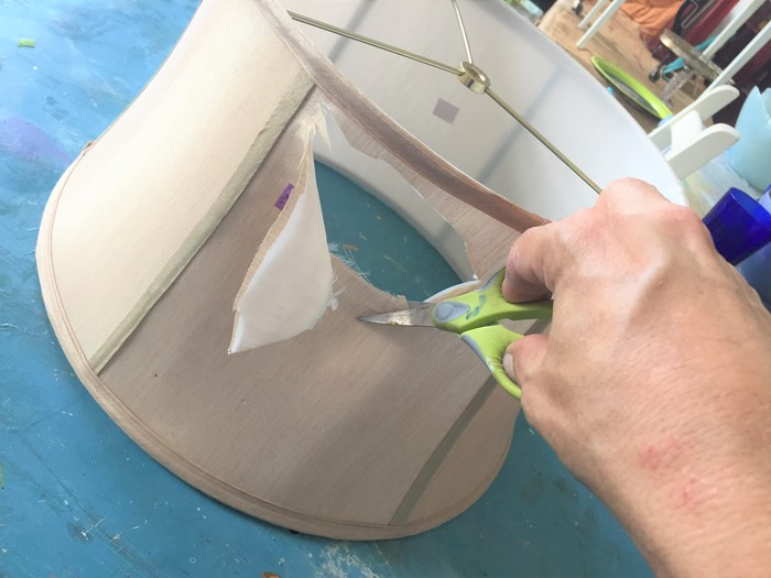 Tim uses scissors to cut away the fabric of the old lampshade