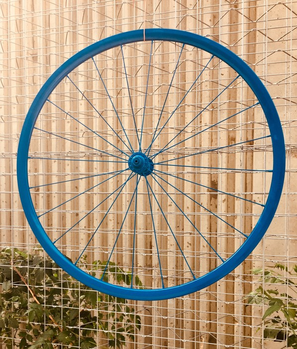 Tim mounts the bicycle wheel using wire.
