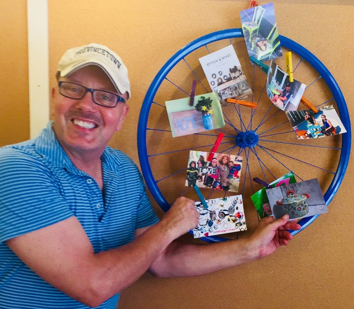 Tim posses with his completed blue bike wheel memo board